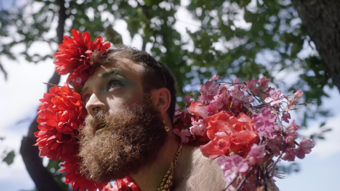 A bearded person adorned in flowers under a tree