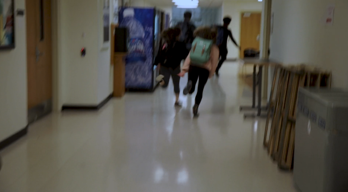 Teenagers run away from the camera in a school hallway