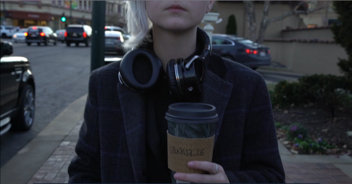 A trans man walks down the street, his coffee cup says Danielle