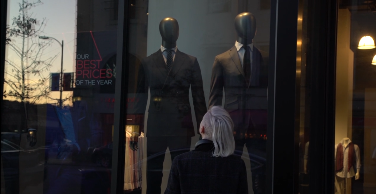 A trans man looks wistfully in a shop window at a suit