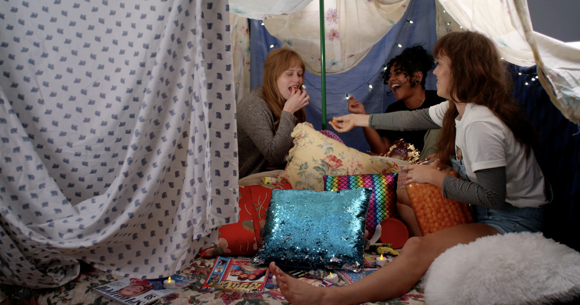 Three friends lounge in a blanket fort chatting