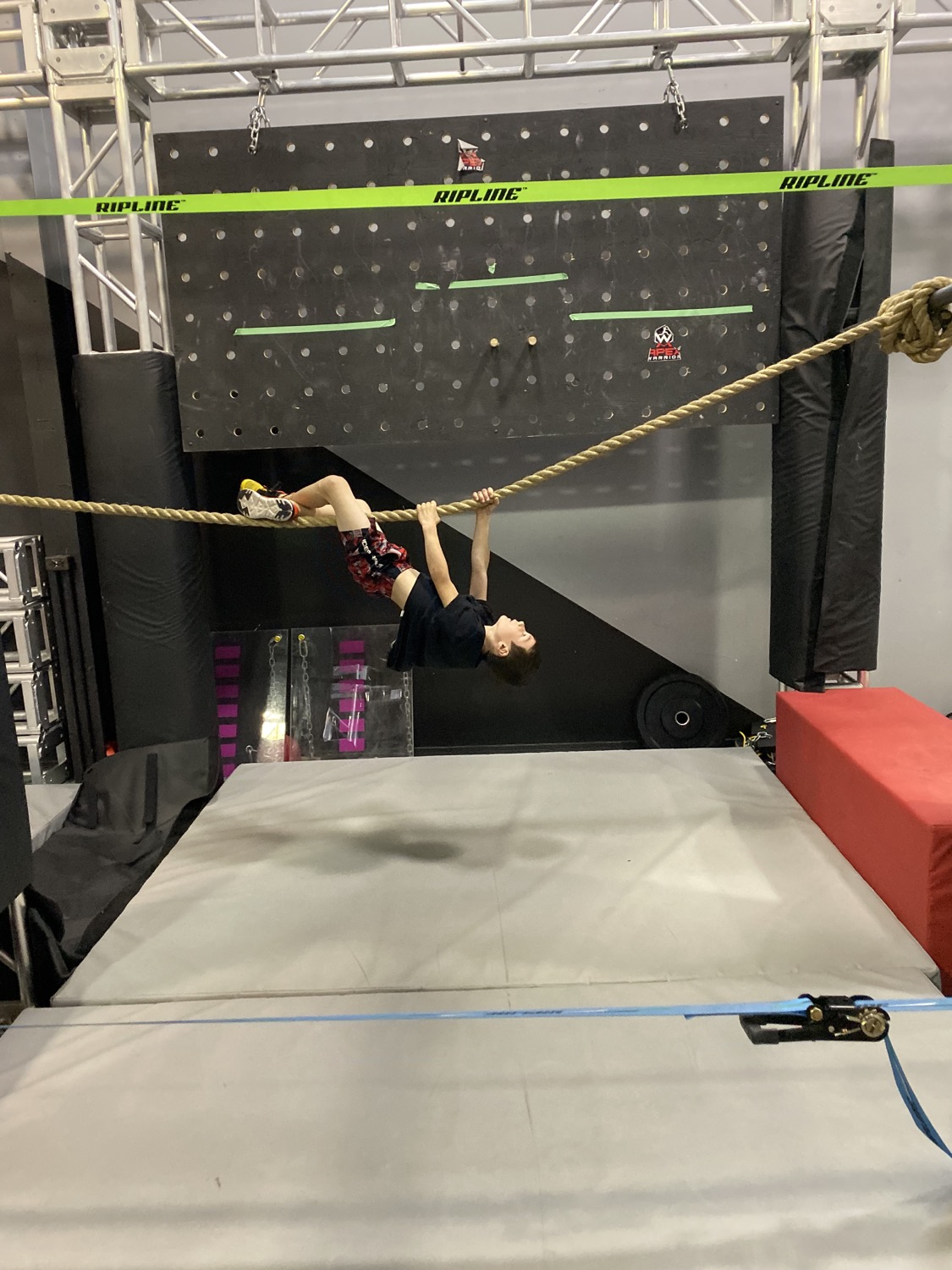 Kid hanging upside down on a rope