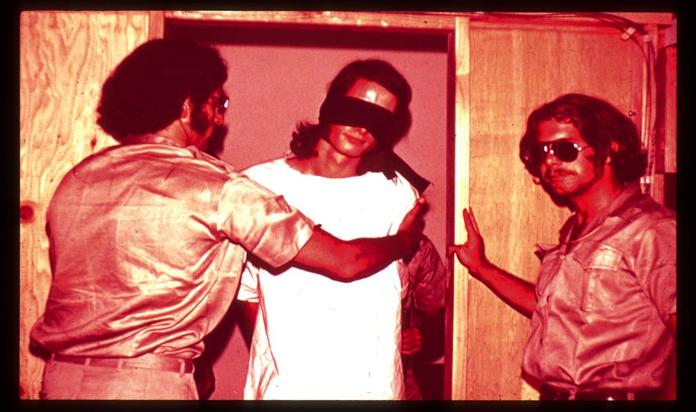 Blind-folded prisoner with guards in the Stanford Prison Experiment