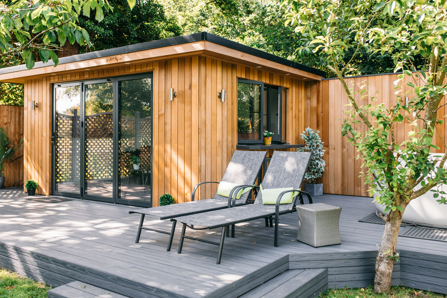 Garden Room surrounded by trees & seats.