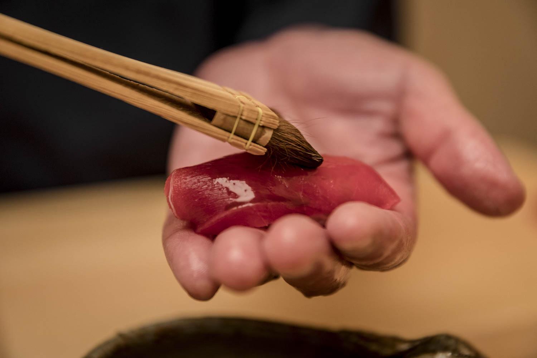 Chef applicant de la sauce sur un sushi