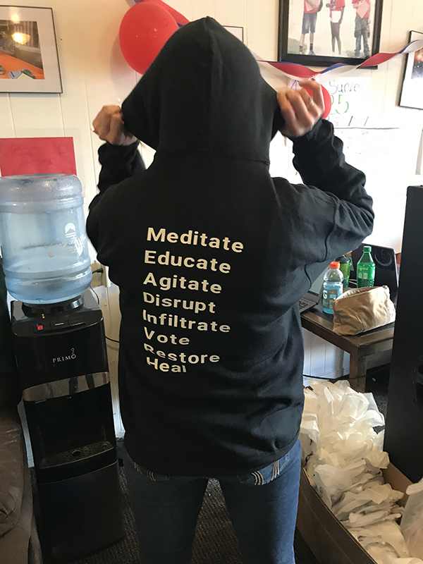 Picture of River Valley Organizing Members backside of their Sweatshirt showing the words Meditate, Educate, Agitate, Disrupt, Infiltrate , Vote , Restore= , Heal