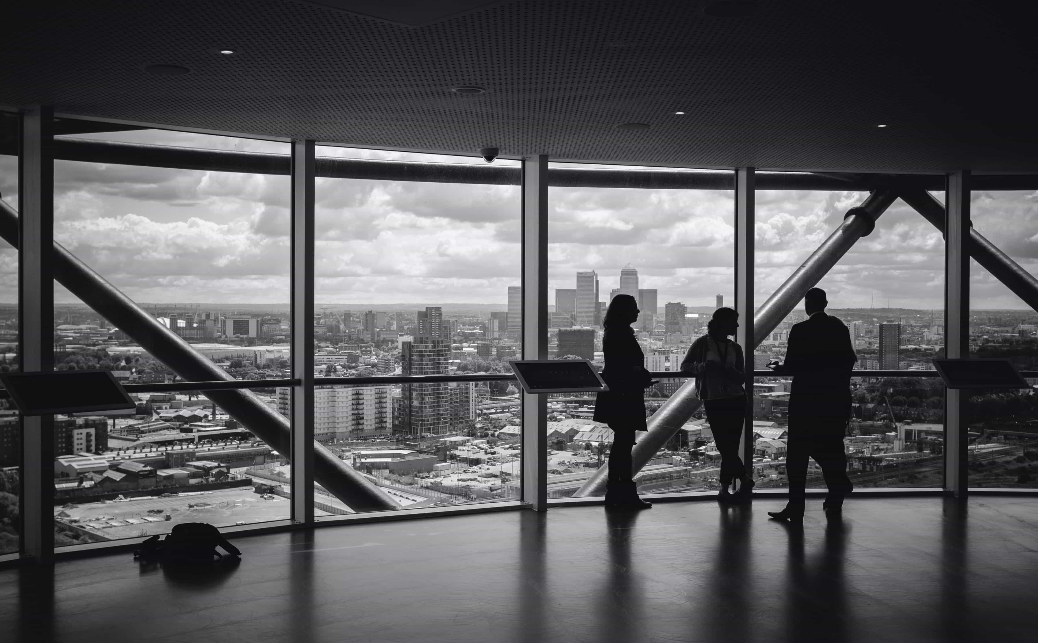 Three people talking in a commercial office building with a view of a skyline