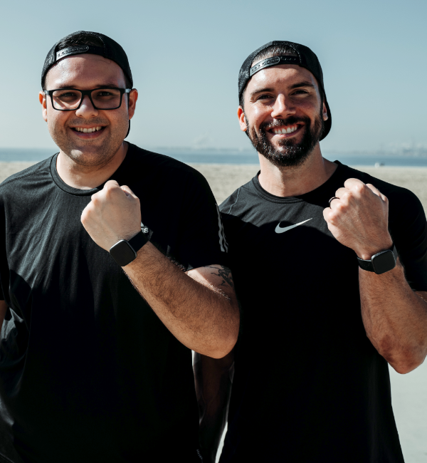 Two men smiling in fitness clothes and showing their smartwatches.