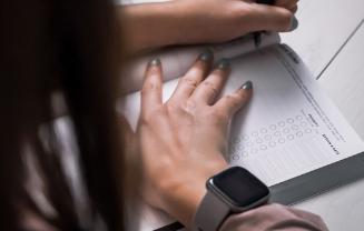 A women writing in a notebook.