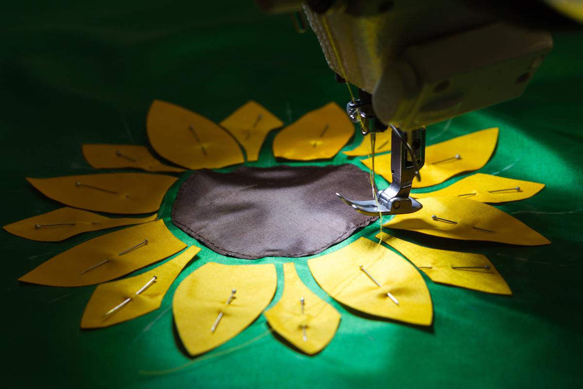Sunflower pattern being machine sewn into racing silks.