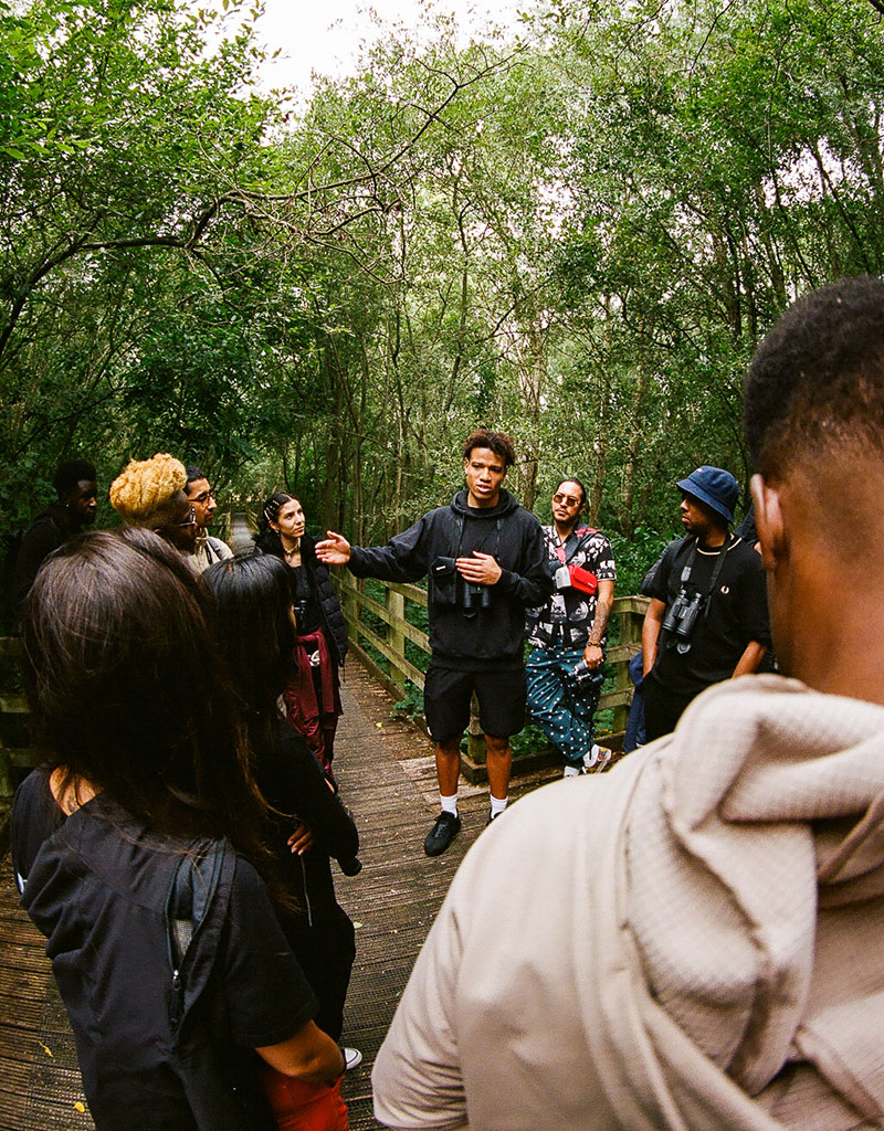 A member of flock together talks to a circle of people in a woodland clearing