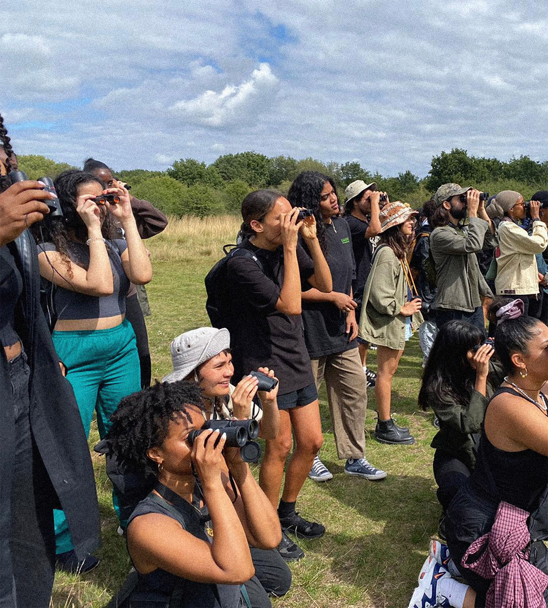 Members of the flock hold binoculars to their faces while looking for birds.