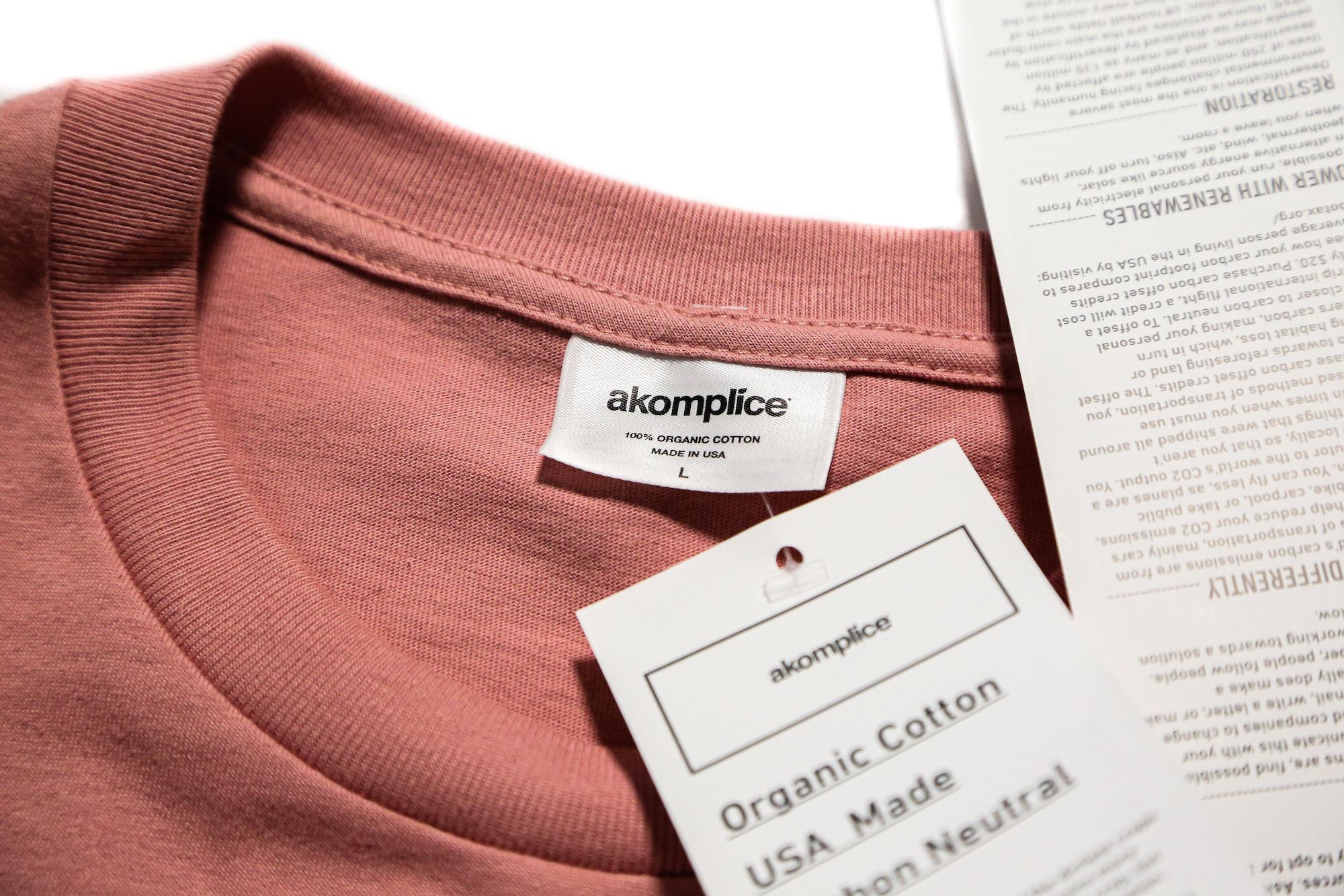 Akomplice custom neck tag and hang tag on red shirt