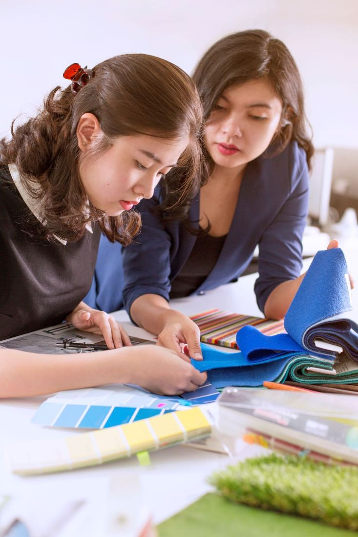 Two team members who are choosing fabrics for an interior design project.
