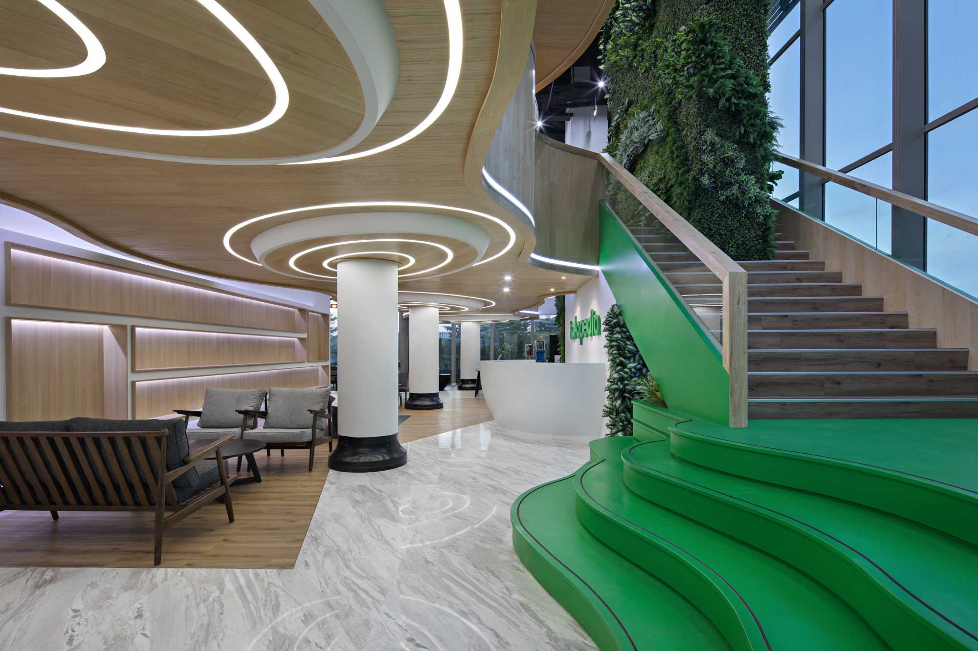 The lobby with internal staircase of the new Tokopedia Care office in Jakarta. Interior Design + Build by AVIP