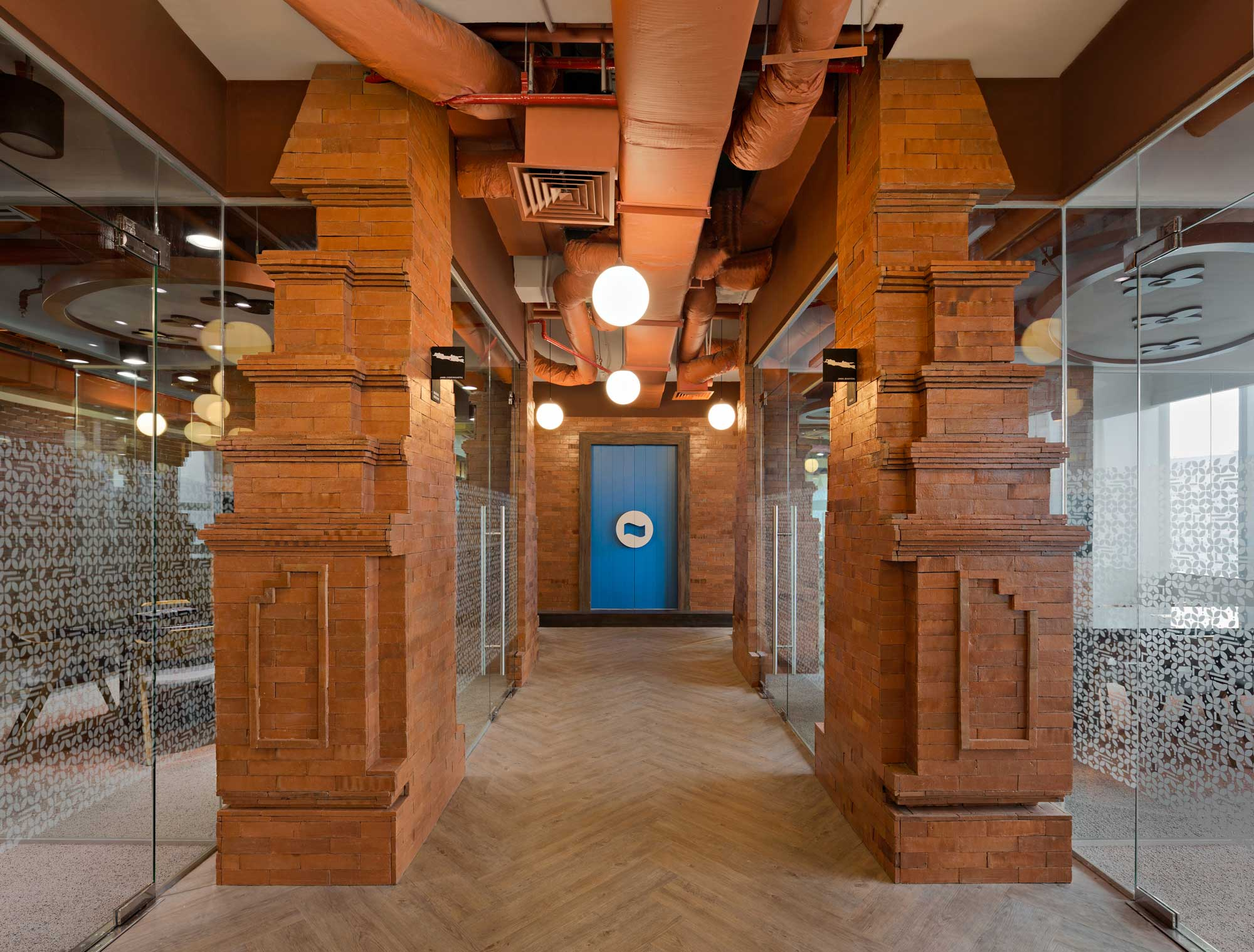 This is a hallway with two meeting rooms on the left and two on the right. Part of the design is a Balinese gate 'Candi Bentar'. Interior Design + Build by AVIP.