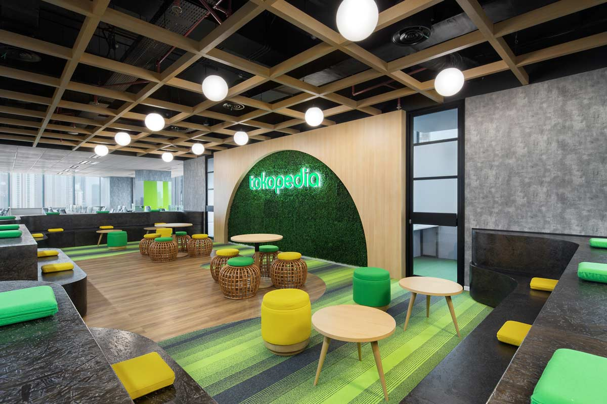 This is the townhall for one floor of Tokopedia's care centre, lot's of seating options and the color scheme is mostly green. Interior Design + Build by AVIP.