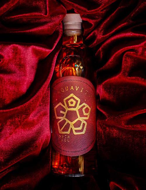 A bottle of MEIR Jul laying on red velvet.