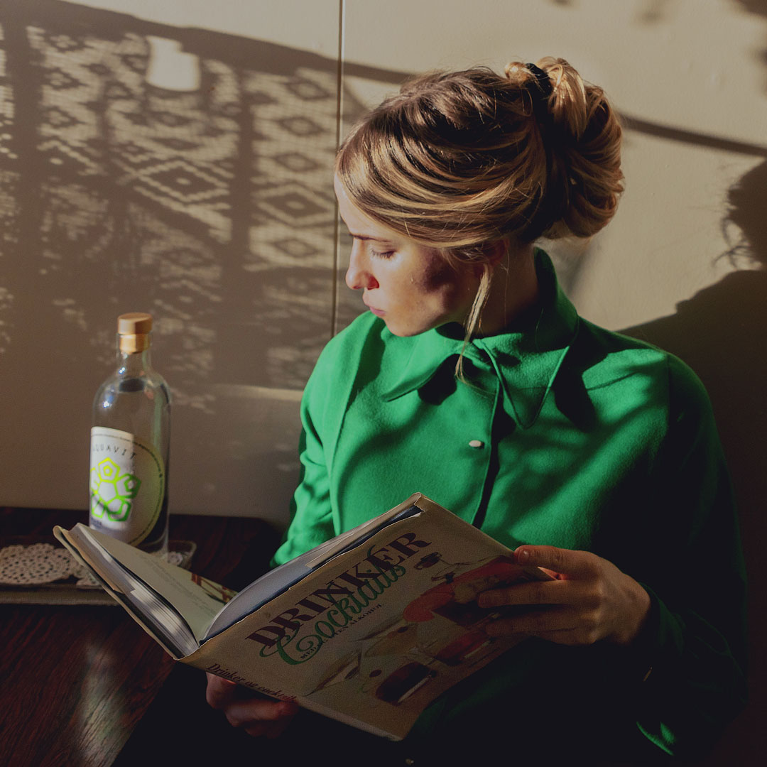A woman reading a cocktail book besides a bottle of MEIR Aquavit No. 1.