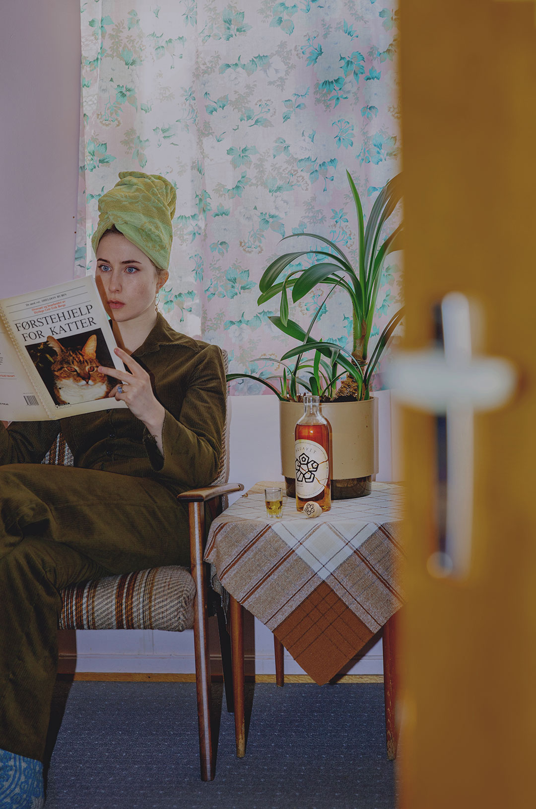A woman reading a book whilst sipping on MEIR Classic aquavit.