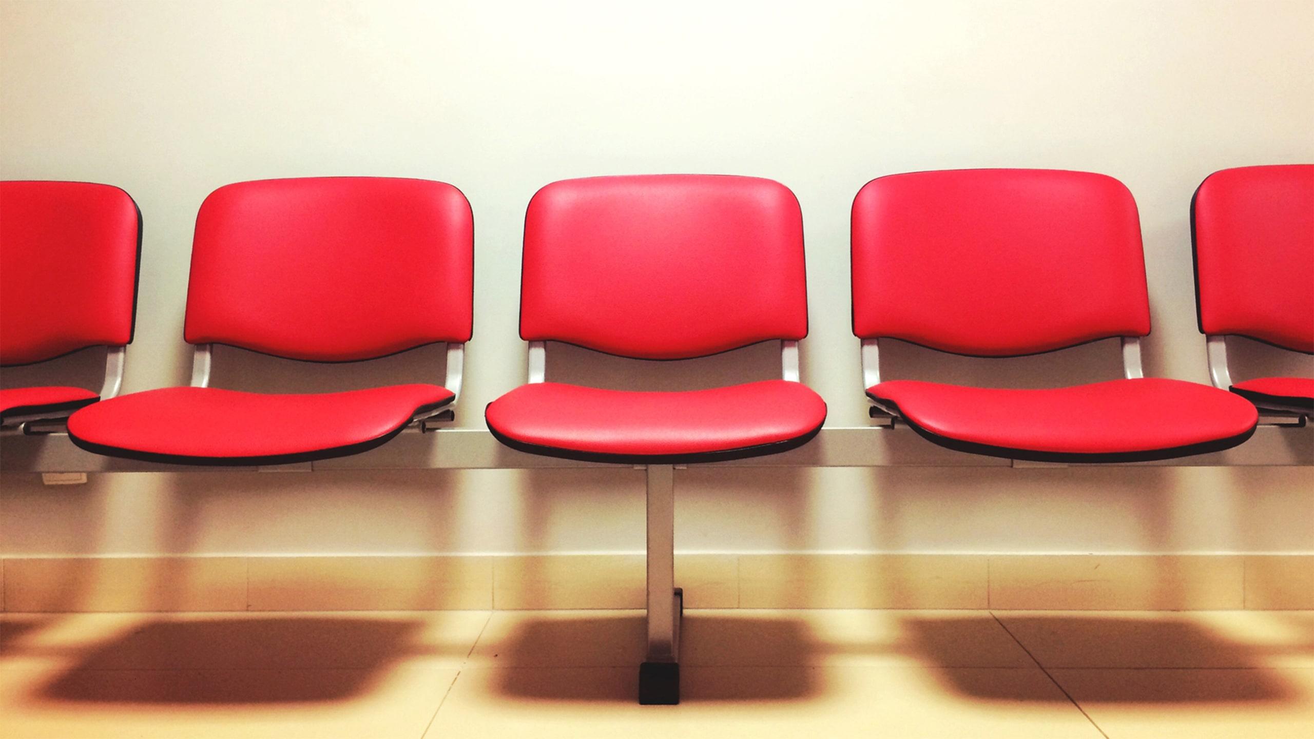 Rode stoelen in een wachtruimte in de zorg