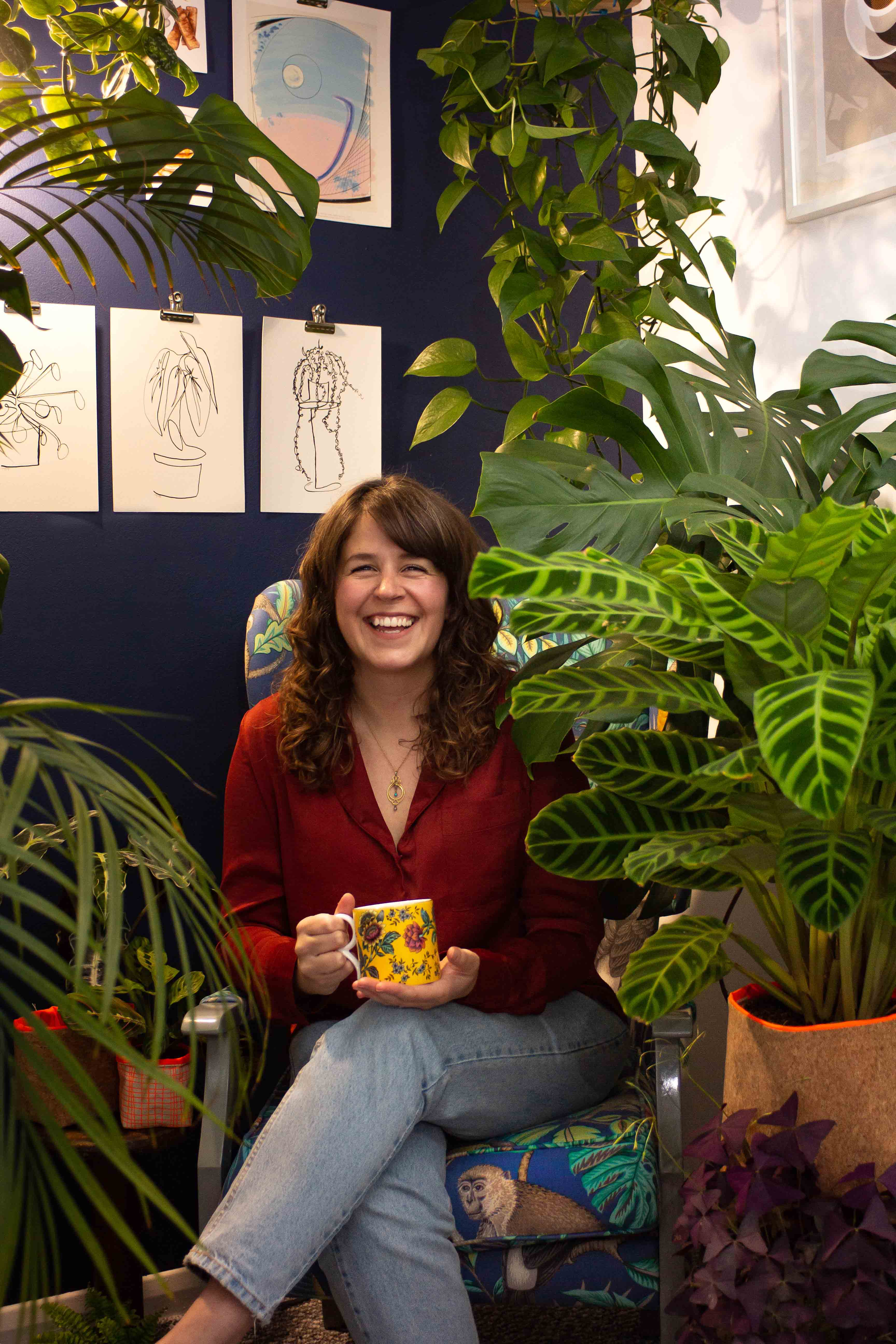 Rosanna Costello is shown in her house plant jungle, with a cup of coffee and a beautiful smile on her face.