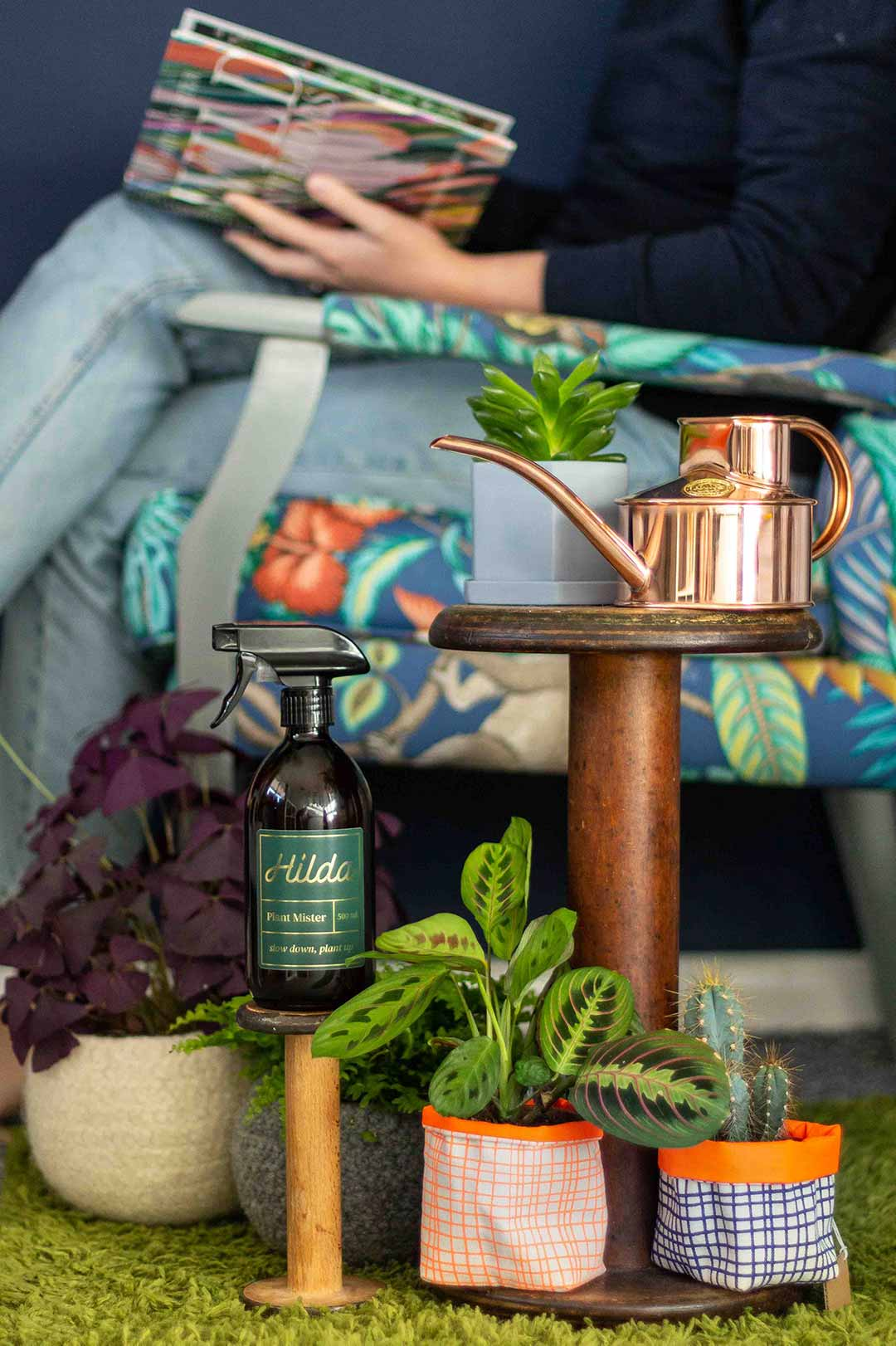 Plants arranged on a side table with a watering can and plant mister. A woman sits in the background on a patterned chair reading a book.