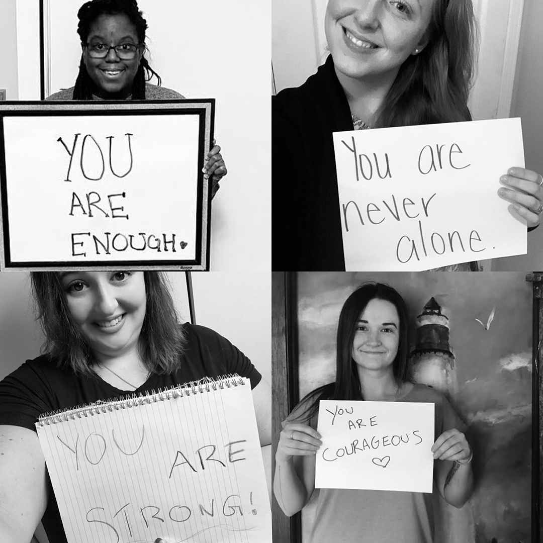 Four different women holding up handwritten, encouraging signs.