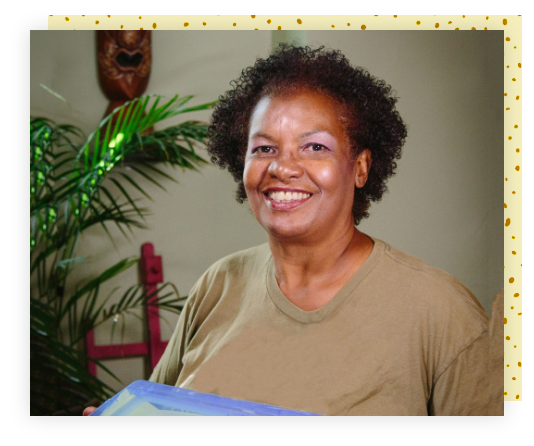 An elderly Black woman smiling as she holds up a blue Shoebox gift.