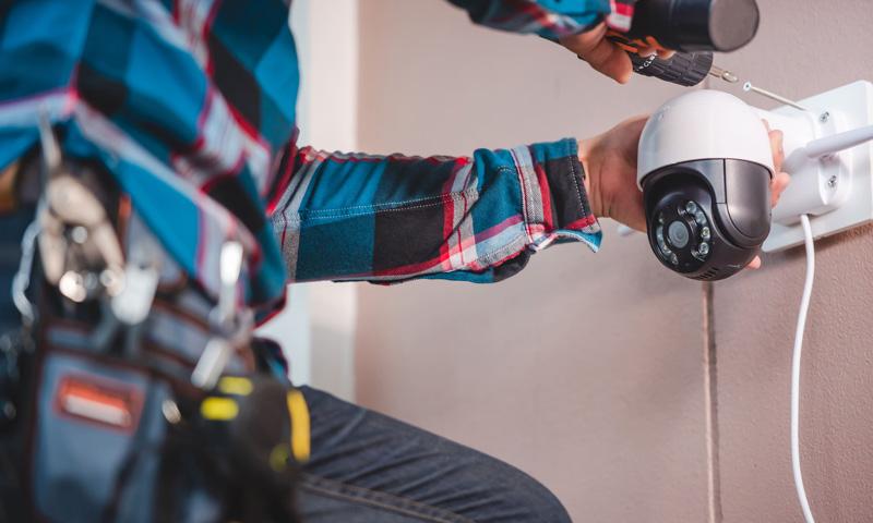 Système d'alarme anti-effraction : un homme installe une caméra