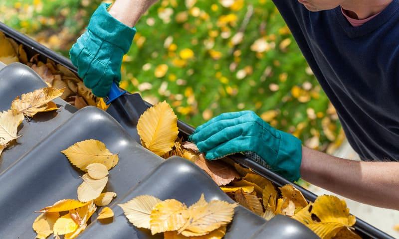 Un homme enlève les feuilles du toit de la maison.