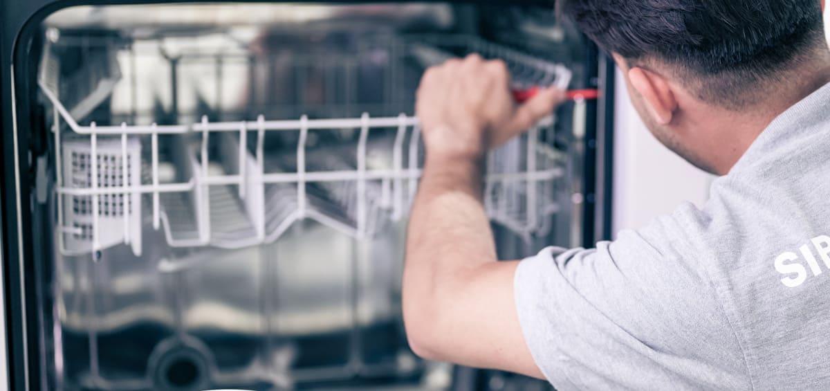 Un technicien de SIBIRGroup répare un lave-vaisselle.