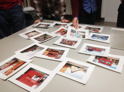 A series of photos are laid out on a table. One person reaches to pick one photo up.