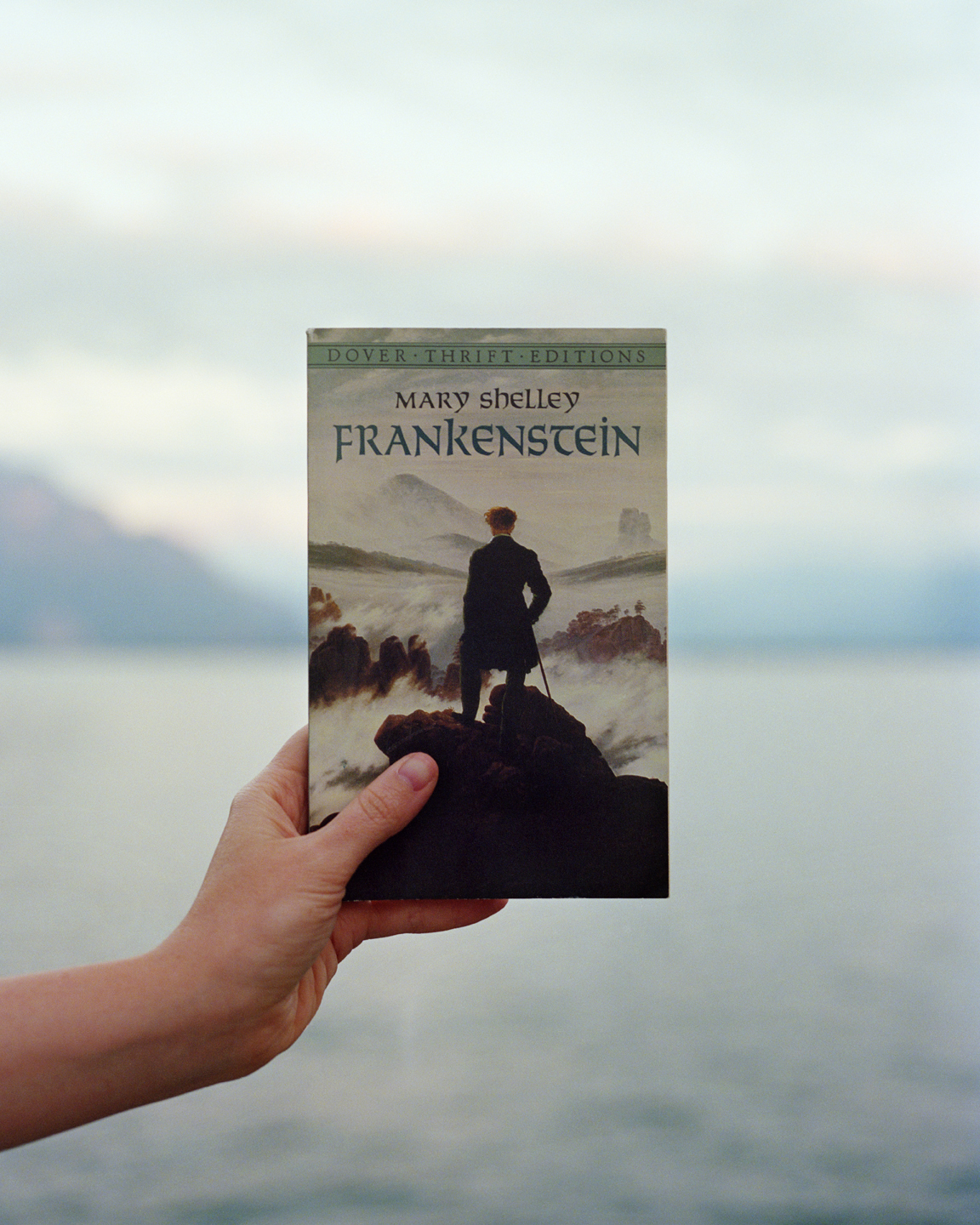 A white woman's hand holds a copy of Mary Shelley's novel Frankenstein, with an image of Caspar David Freidrich's painting Wanderer Above the Sea and Fog as its cover, in front of Lake Geneva.