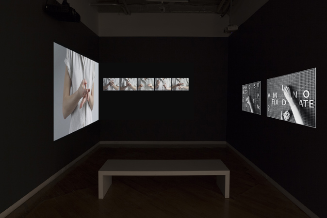 Image of Proof 26 at Gallery 44. The image is of the back gallery which is painted competely Black with a three channel video projection of hands gesturing sign language.