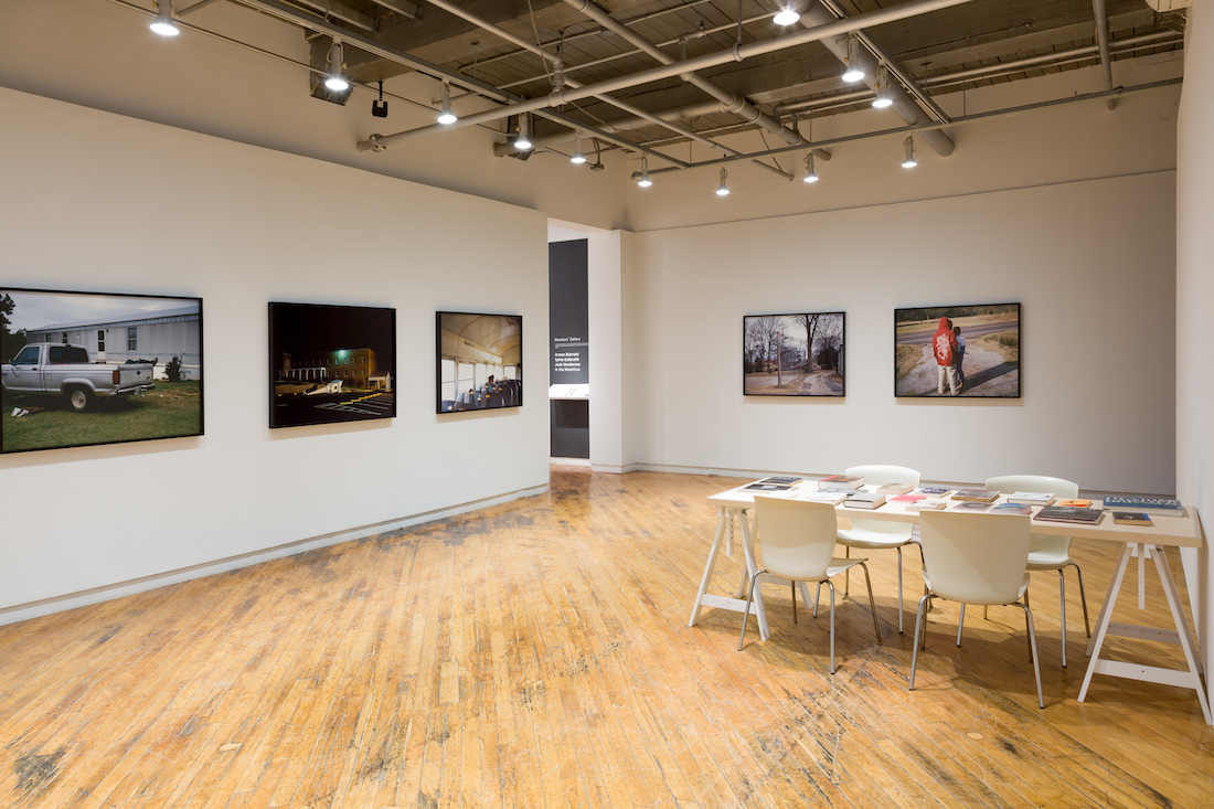 Main gallery space with large framed photographs and a table with books.