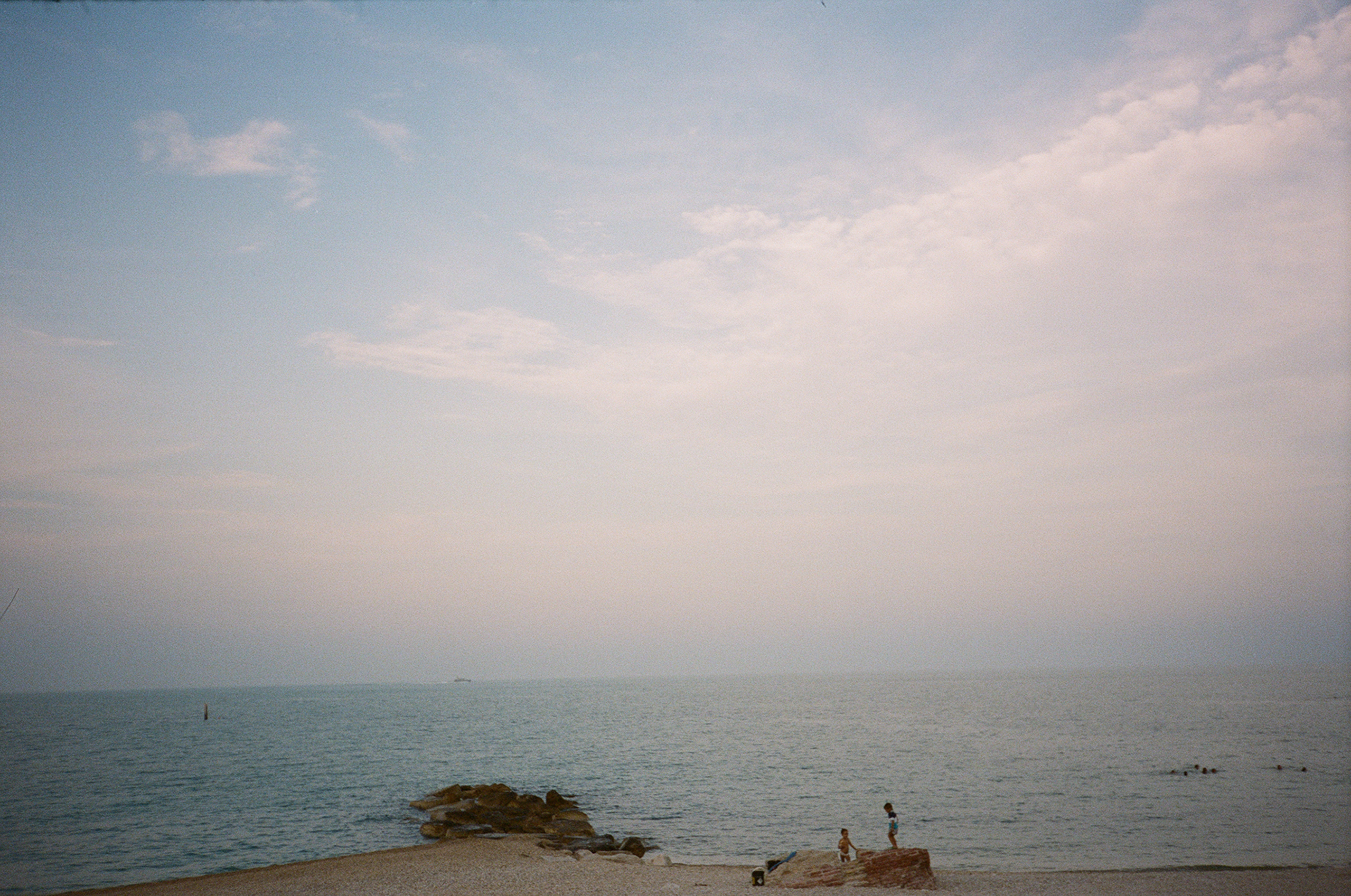 Landscape film photograph of a body of water, three kids on shore, some swimming