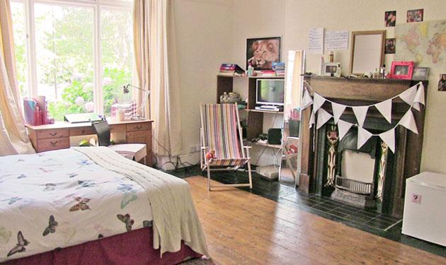 The huge ground floor bedroom with its wooden floor and beautiful original fireplace