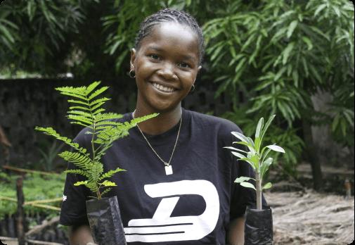 Women holding 2 tree saplings smiling