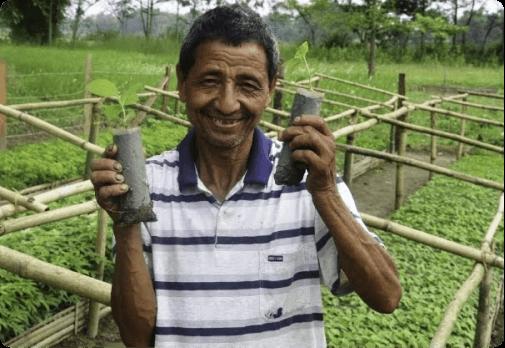 Hondura Man holding 2 tree saplings smiling