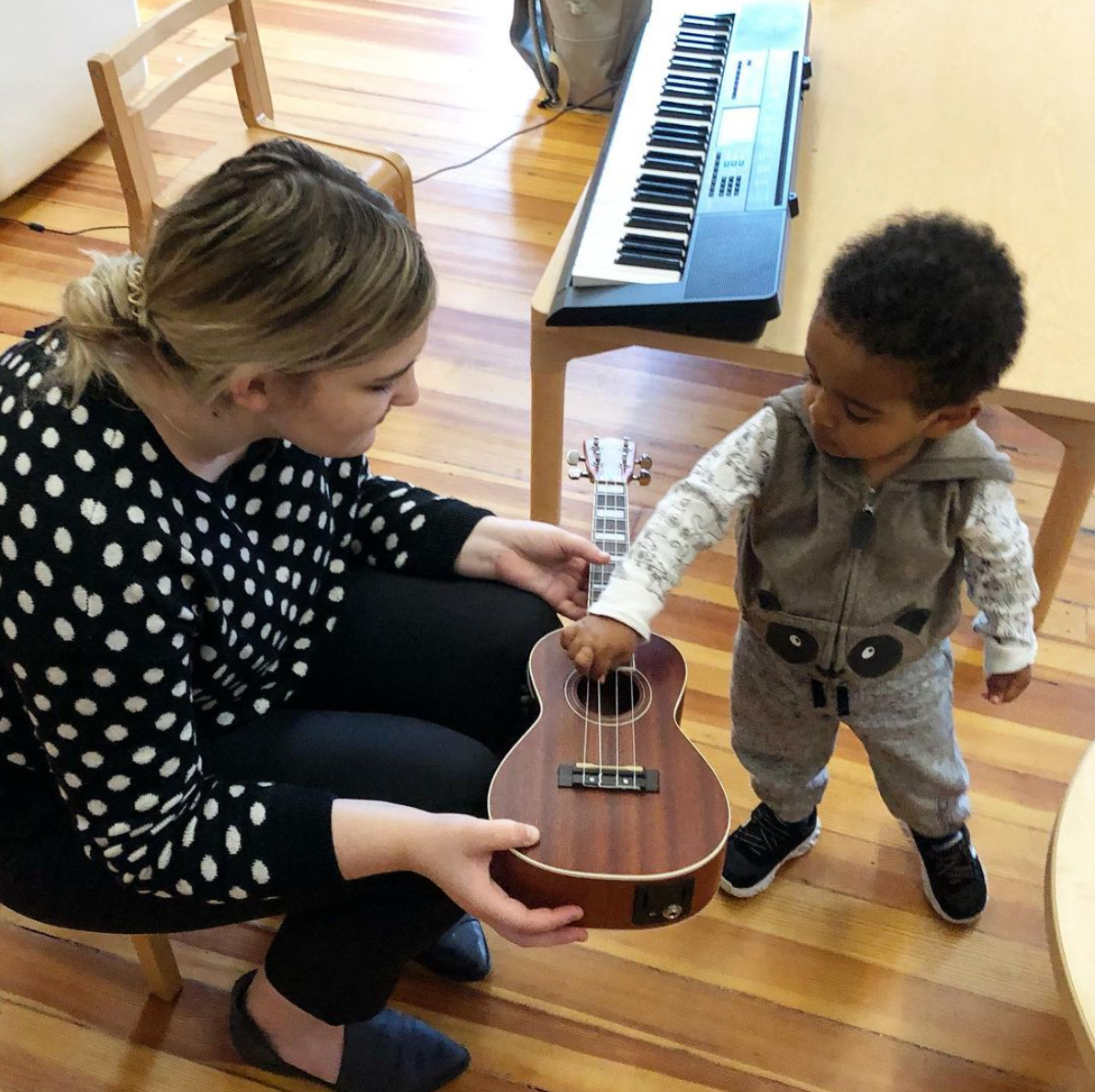 A music teacher holds a ukulele for a young child to play with