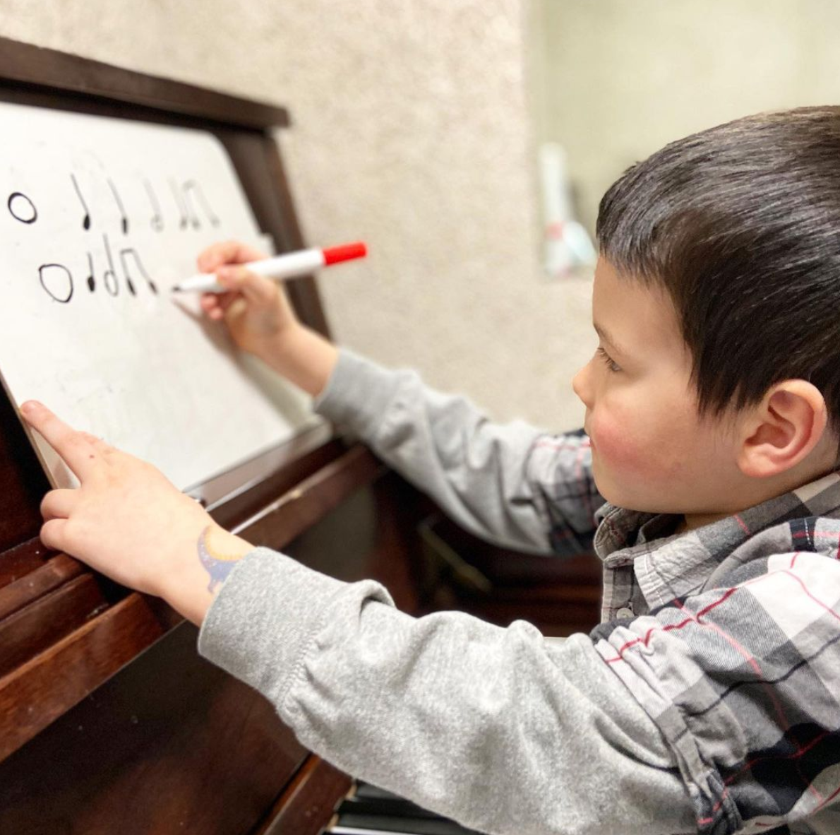 A young boy uses a marker to draw music notes on a sheet of paper while sitting at a piano