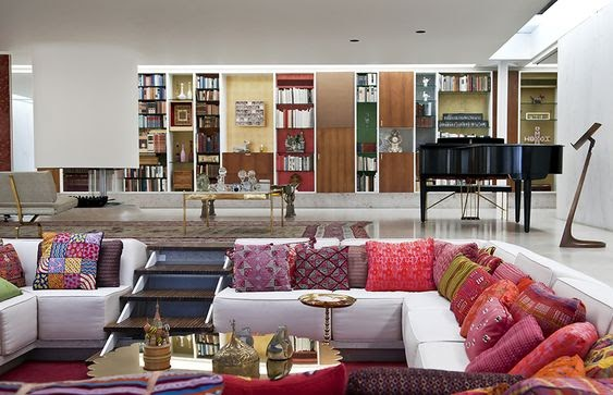 A split level living room with bright pink pillows, making the space distinctive from the nude-toned room behind it