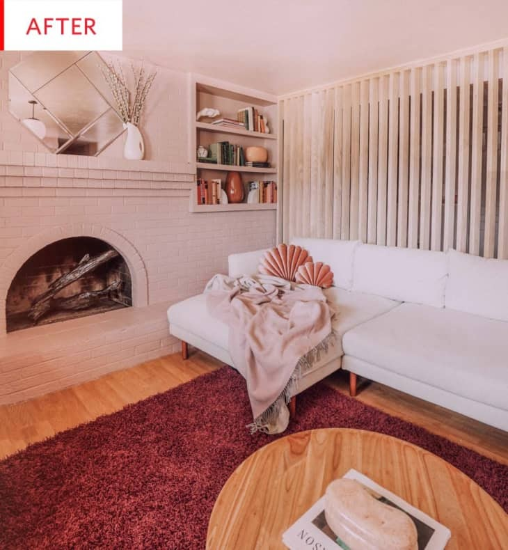 An after photo of the same living room, now with blush-painted bricks and a white, plush sofa