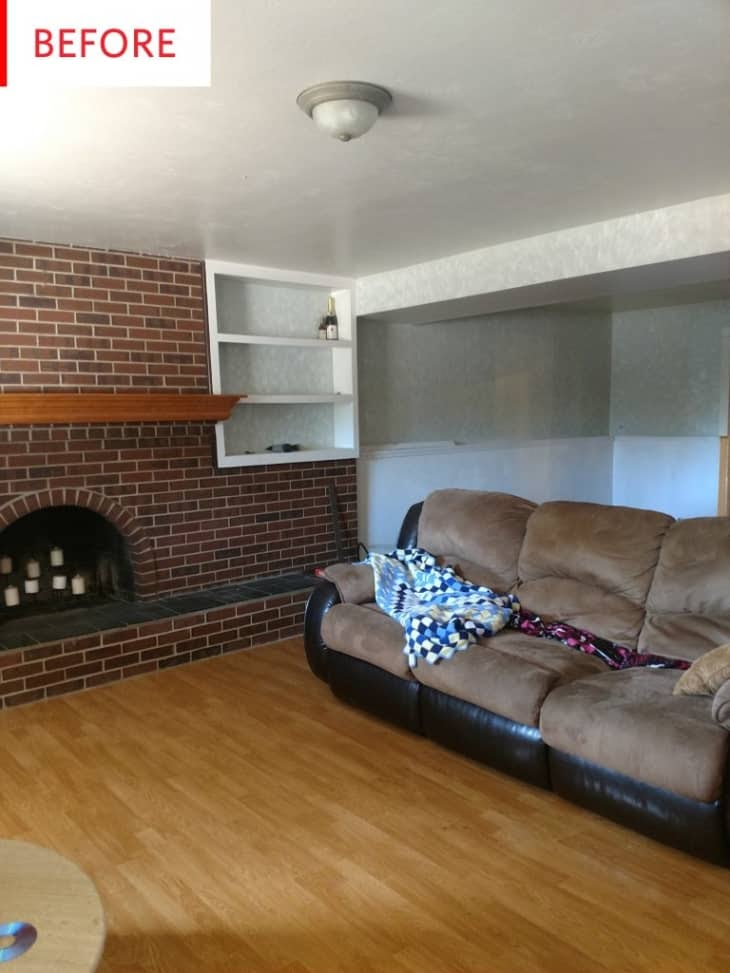 A before picture of a split level living room with a brick wall and a leather couch