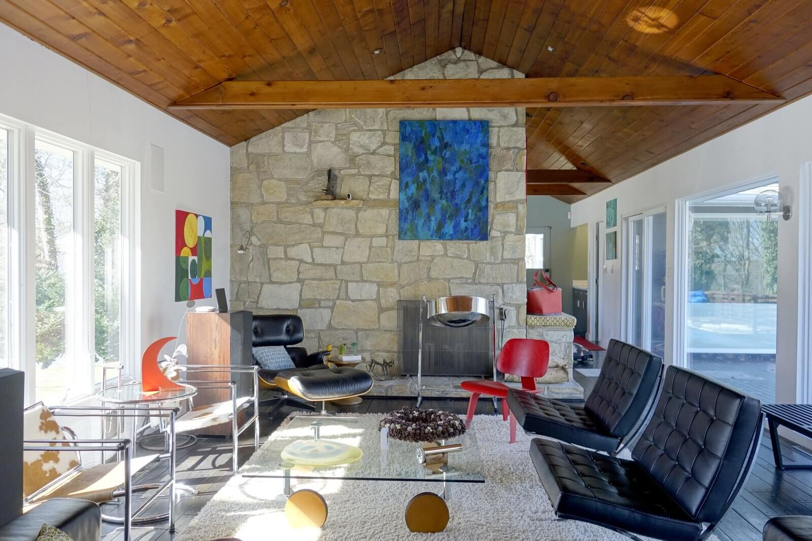 A ranch house living room with unique couches, a glass table, and distinct paintings