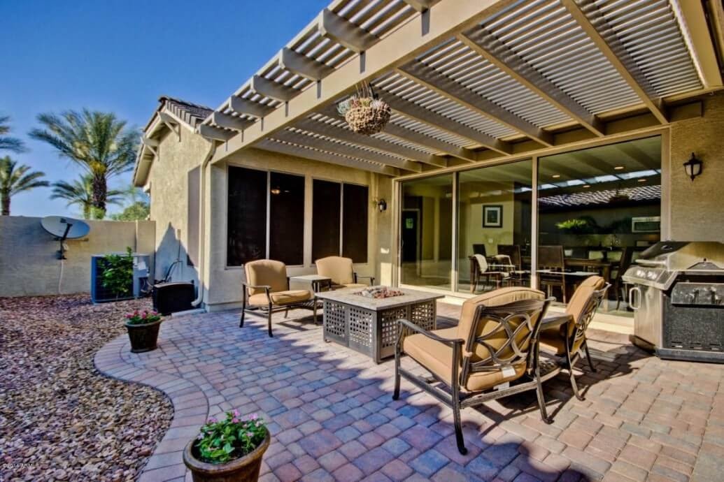 A ranch house patio that is flat, lined with stone, and decked out with nice furniture