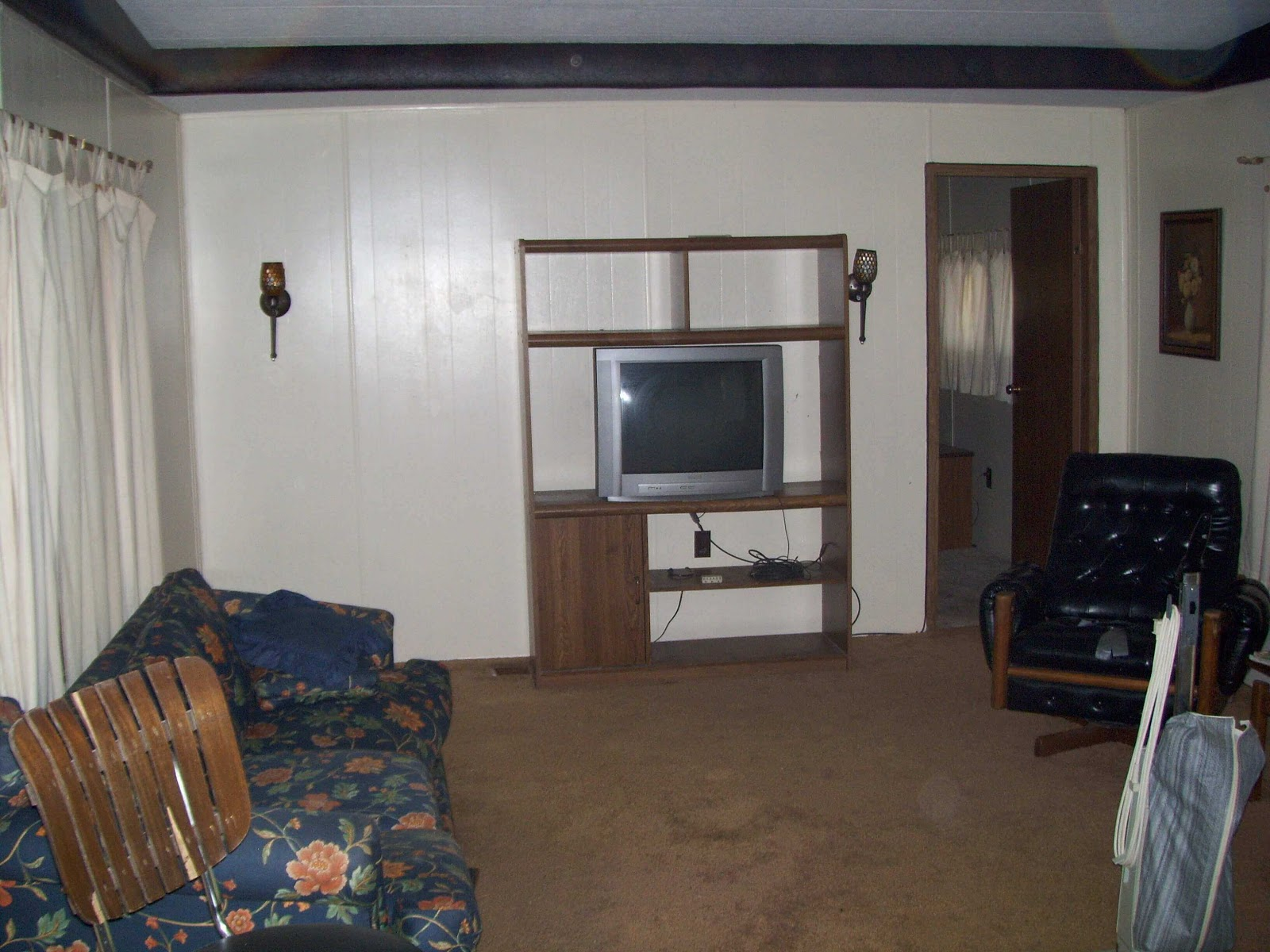 The before picture of a manufactured home, with an old television and television set and old furniturel