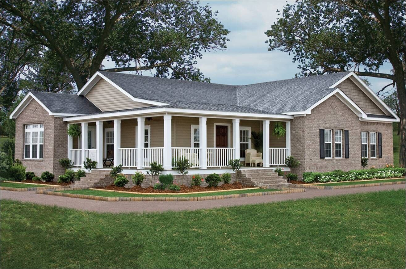 A manufactured home remodel with a beige brick exterior and a large lawn