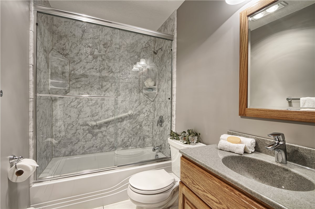 A shower tub remodel with a glass sliding door instead of curtains to brighten up the bathroom